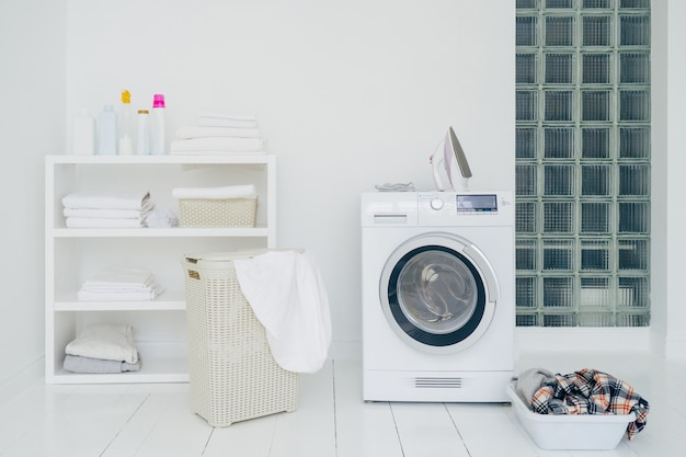 Laundry room with washing machine, dirty clothes in basket, iron and little shelf with neatly folded linen. domestic room interior. washing concept Premium Photo