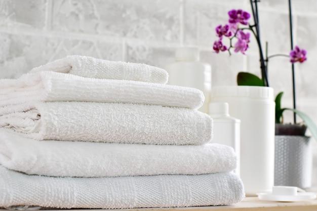 Бельё, белые контейнеры для моющих средств, макет и стопка белых полотен Premium Фотографии