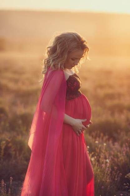 Красивая беременная женщина провансали ослабляя в поле лаванды наблюдая на заходе солнца держа корзину с цветками lavanda. серии. соблазнительная девушка с фиолетовой лавандой. блондинка в цветущем поле Premium Фотографии