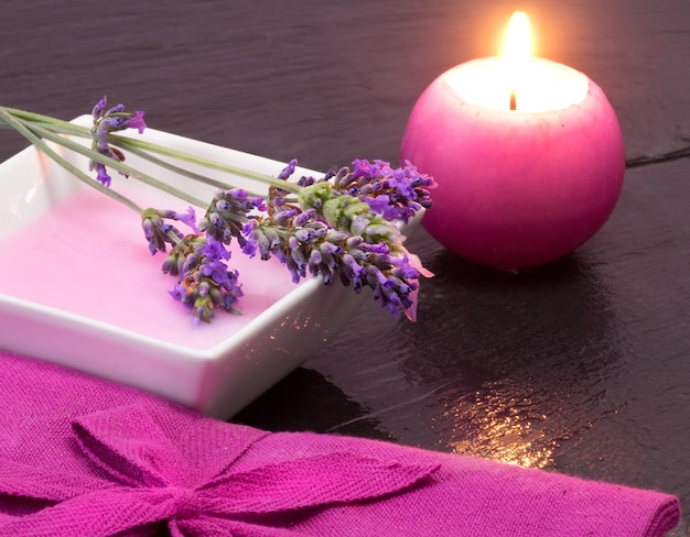 Lavender bath foam with scented candle and flowers Premium Photo