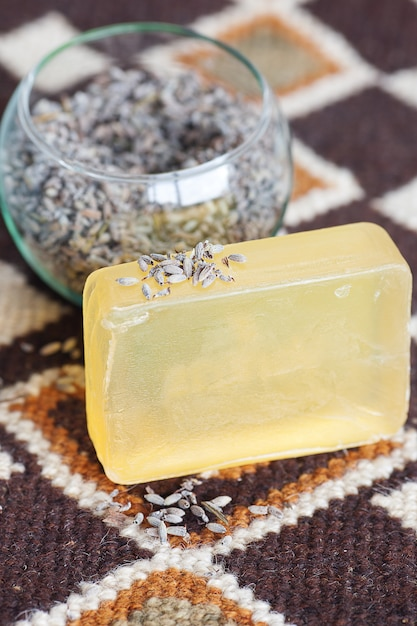 Lavender in bowl and soap on ethnic mat Premium Photo