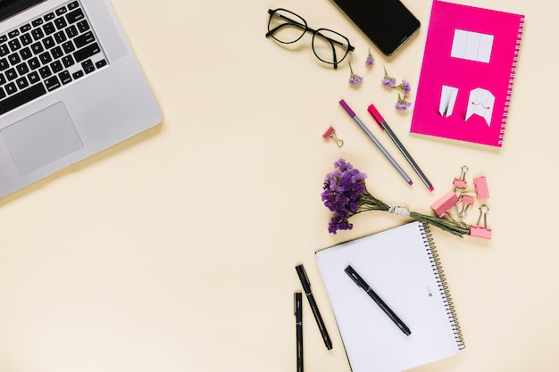 Lavender flower bunch with stationeries and laptop on beige background Free Photo