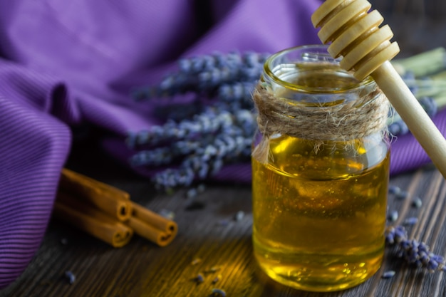 Lavender and herbal honey in glass jar on dark wooden table. Premium Photo