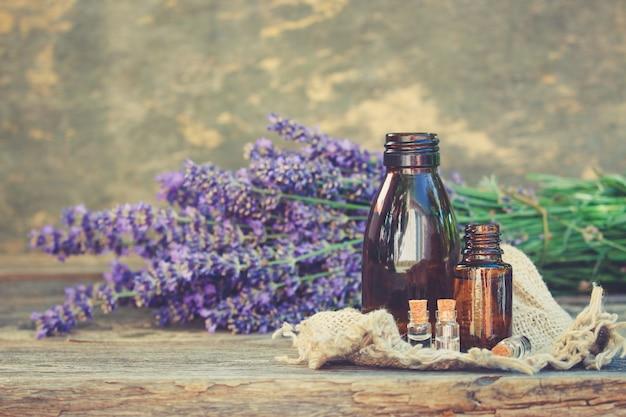 Lavender oil in different bottles on wooden background. Premium Photo