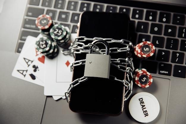 オンラインカジノのコンセプト、南京錠付きスマートフォン、キーボードのポテトチップスに関する法律と規則 Premium写真