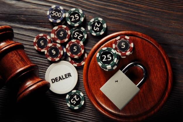 オンラインギャンブルの概念に関する法律と規則、木製の表面に南京錠とエースで小槌を判断する Premium写真