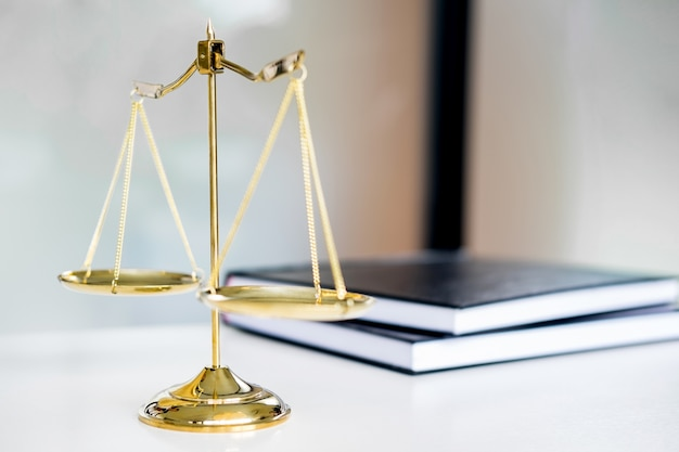 law scales or golden weight and legals books on table. symbol of