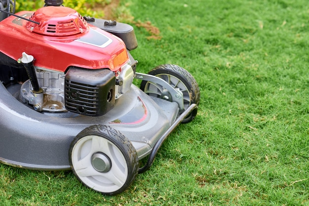 Lawn  mover on green grass in a garden close up Premium Photo
