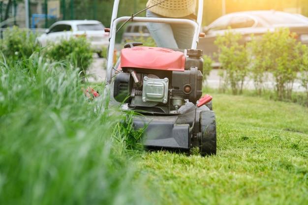 Lawn mower cutting green grass, gardener with lawnmower working Premium Photo