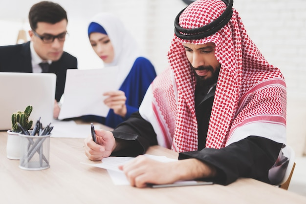 Lawyer is talking to woman. arab is writing. Premium Photo