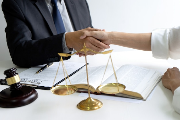Lawyer or judge with gavel and balance handshake Premium Photo