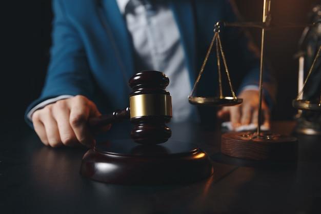 Адвокатская контора. статуя правосудия с весами и юристом, работающим на ноутбуке. юридическое право, консультации и концепция правосудия. Premium Фотографии