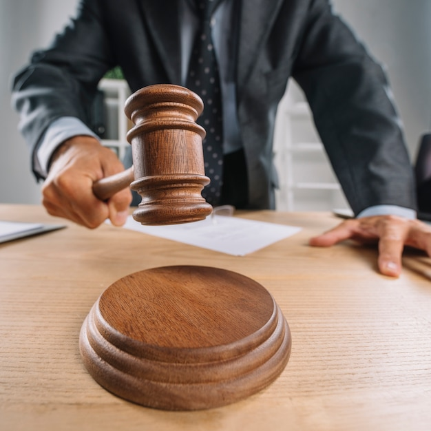 Lawyer's hand hitting wooden gavel on sounding block Free Photo