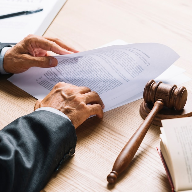 Lawyer's hand holding document with gavel and mallet on wooden desk Free Photo