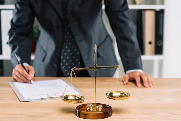 Юрист подписывает контрактный документ перед шкалой правосудия над столом Premium Фотографии