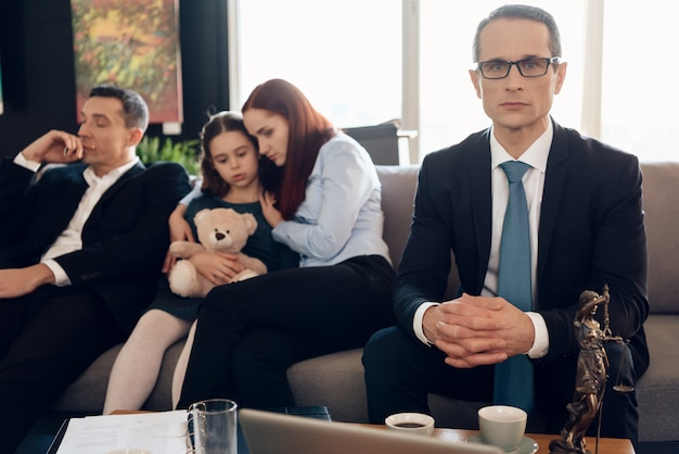Lawyer sits on couch next to upset family. Premium Photo
