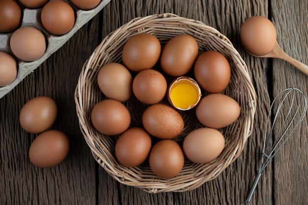 Положите яйца в деревянную корзину на деревянный пол. Бесплатные Фотографии
