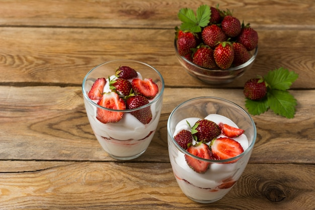 Layered strawberries cream cheese dessert on wooden background Premium Photo