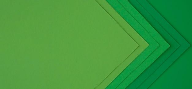 Strati di libri verdi che creano frecce astratte Foto Gratuite