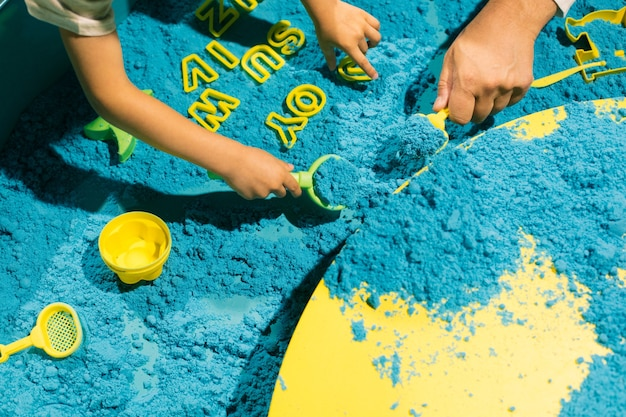 Laying out words with help of blue kinetic sand.. development of fine motor skills. modern educatio