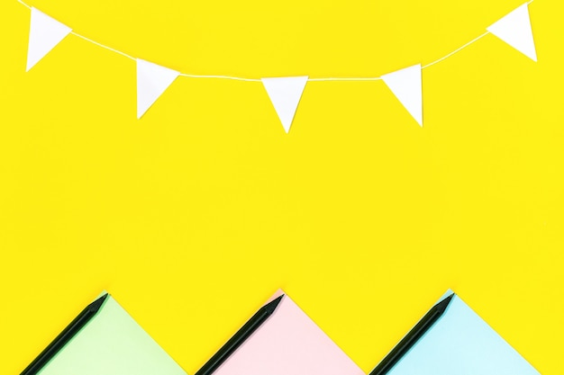 The layout of the colored paper, black pencils and a garland of white flags located on yellow. Premium Photo