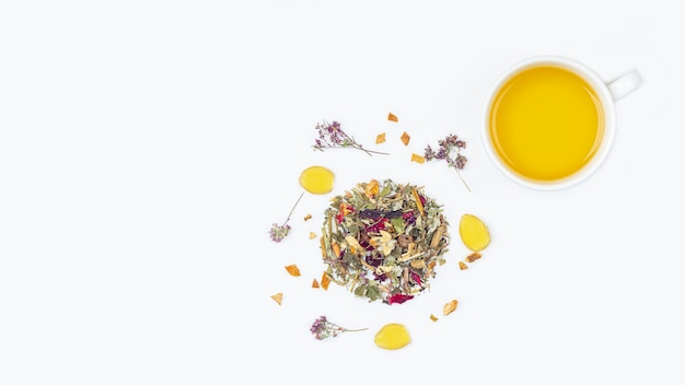 Layout of cup of green tea with assortment of different dry tea leaf and flower petals on a white background Premium Photo