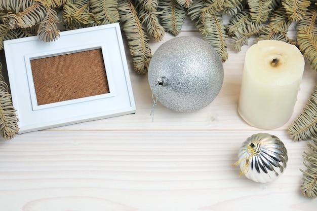 흰색 나무 테이블에 크리스마스 테마에 사진 프레임, 종이, 연필의 레이아웃 프리미엄 사진
