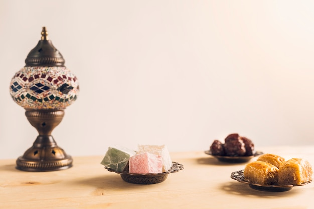 Layout of prunes near baklava and turkish delights on saucers Free Photo