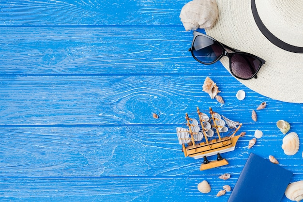 Layout of seashells near toy ship and sunglasses with hat Free Photo