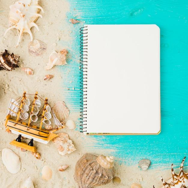 Layout of seashells and toy ship among sand near notebook Free Photo