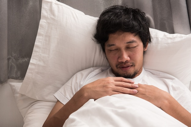 Laziness of asian man that still sleeping on the bed in bedroom in morning, time to wake up. Premium Photo