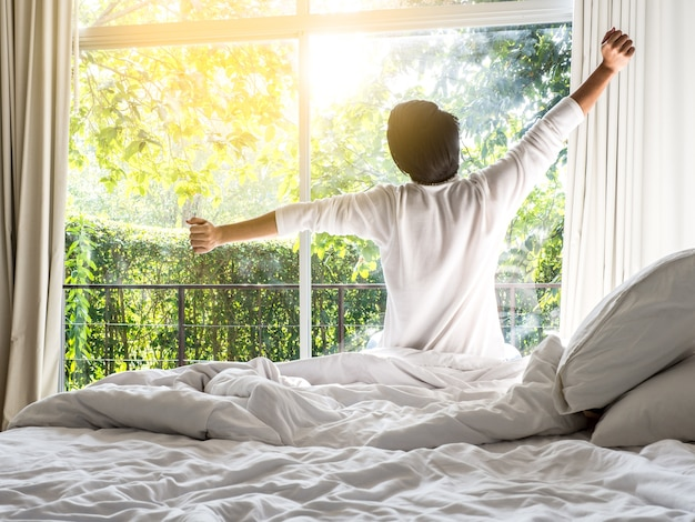 Lazy man happy waking up in the bed rising hands in the morning with fresh feeling Premium Photo
