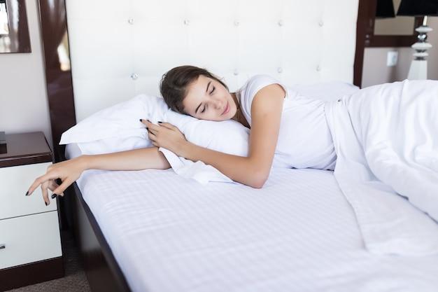 ホテルやファッションのアパートで白いベッドの服を着て広いベッドでブルネットのモデルの女の子を笑顔で怠惰な朝の週末 無料写真