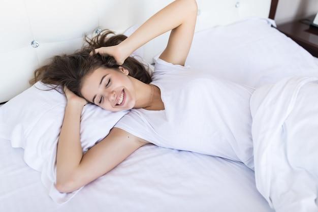 Fine settimana pigro mattutino per sorridente ragazza modello bruna in ampio letto con lenzuola bianche in hotel o appartamento di moda Foto Gratuite