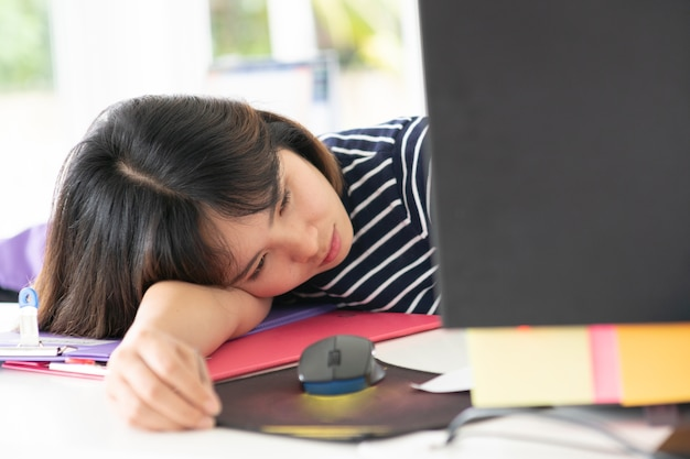 Lazy working in office.woman working on office desk. Premium Photo