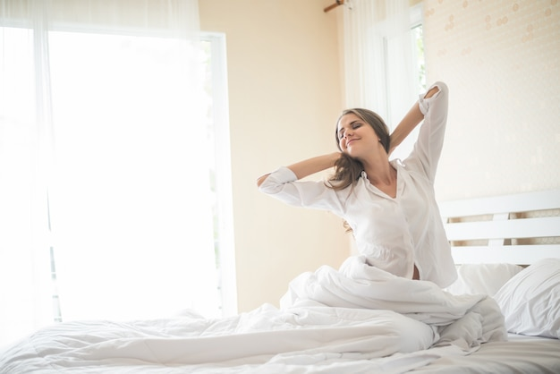 Lazy young woman sitting in bedroom Free Photo
