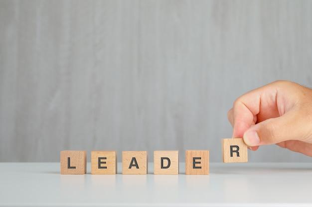 Концепция лидерства на серый и белый стол вид сбоку. рука, собирание деревянный куб. Бесплатные Фотографии