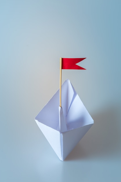 Leadership concept using  paper ship with red flag on blue Premium Photo