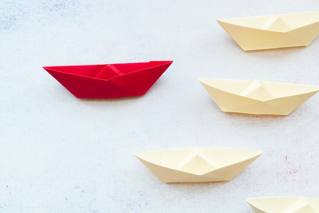 Leadership concept using red paper ship among white on backdrop Free Photo