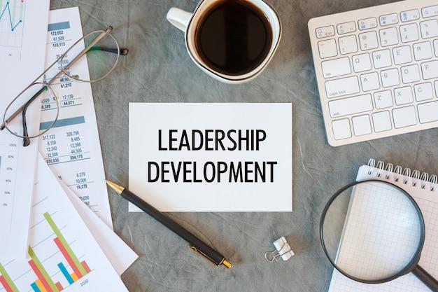 리더십 개발은 사무실 액세서리, 커피, 다이어그램 및 키보드와 함께 사무실 책상에 문서로 작성됩니다. 프리미엄 사진