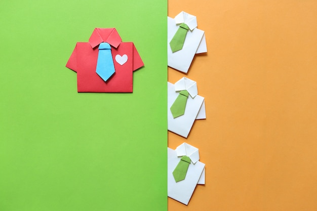 Leadership and teamwork concept, origami red shirt with tie and leading among small yellow shirt Premium Photo