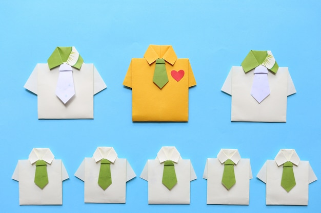 Leadership and teamwork concept, origami yellow shirt with tie and leading among small yellow shirt Premium Photo