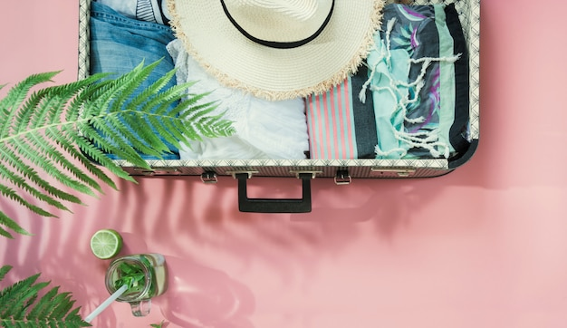 Leaf of fern, tropical detox water and open suitcase with clothes on pastel pink. Premium Photo