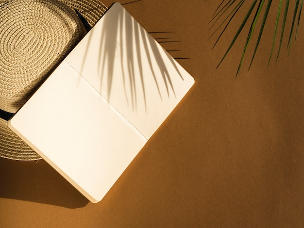 Leaf shadow on a beige background and a notebook and a hat Free Photo