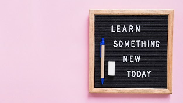Learn something new today text on slate with pen and eraser over pink background Free Photo