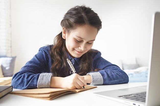 Learning, education, leisure, hobby and modern technologies. cheerful positive teenage girl sitting at desk in her room, making notes in her diary Free Photo