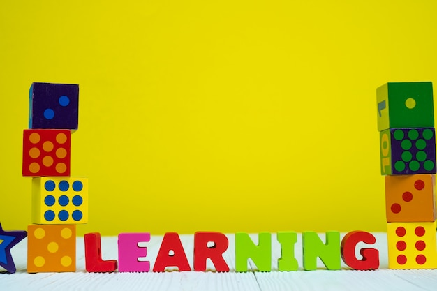 Learning text alphabet and toy square block puzzle on table with yellow background Premium Photo