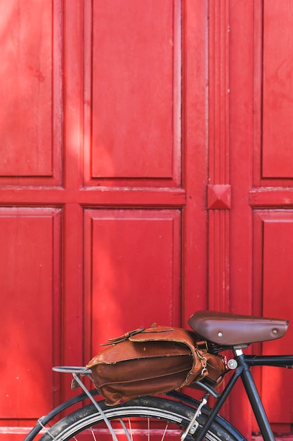 Leather bag on bicycle against red door Free Photo