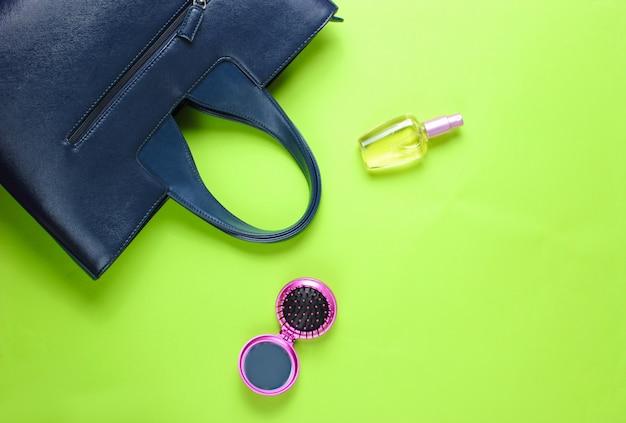 Кожаная сумка, флакон духов, расческа-зеркало на фоне зеленой бумаги Premium Фотографии