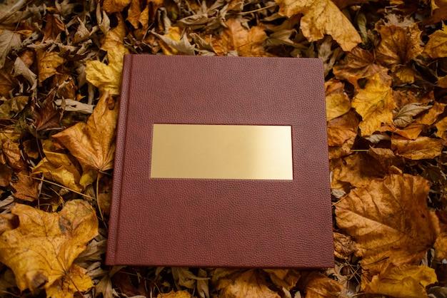 Кожаная коричневая книга с золотой табличкой с коричневыми листьями. место для текста. Premium Фотографии